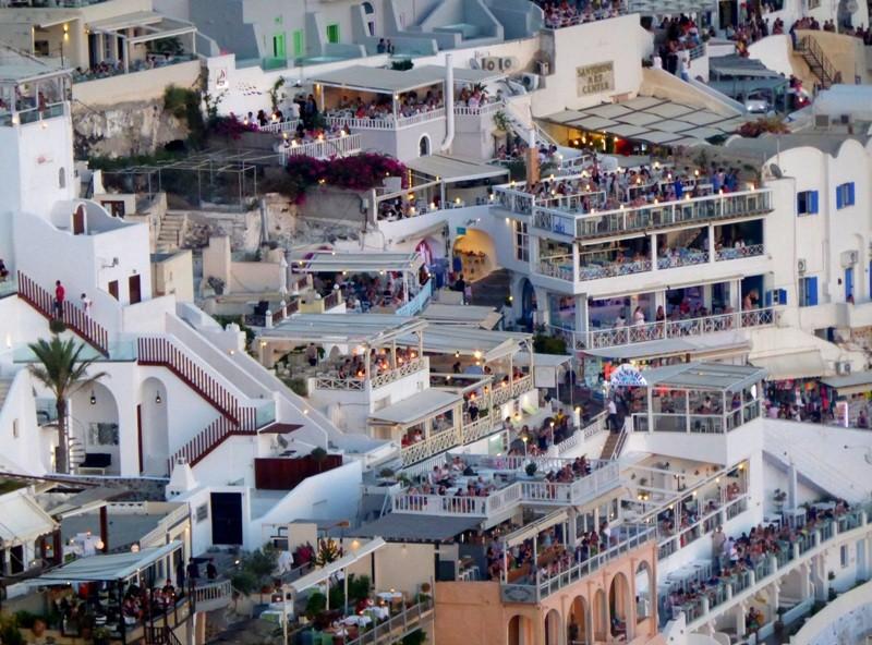 Varandas e restaurantes em Firá em Santorini, com a multidão de turistas esperando o pôr do sol